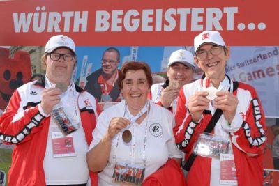 4 Athleten posieren mit ihren Medaillen