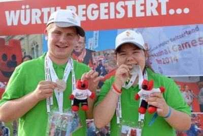 2 Athleten zeigen ihre Medaillen